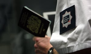 A UK Border Agency officer checks a passport in the north terminal of Gatwick airport.