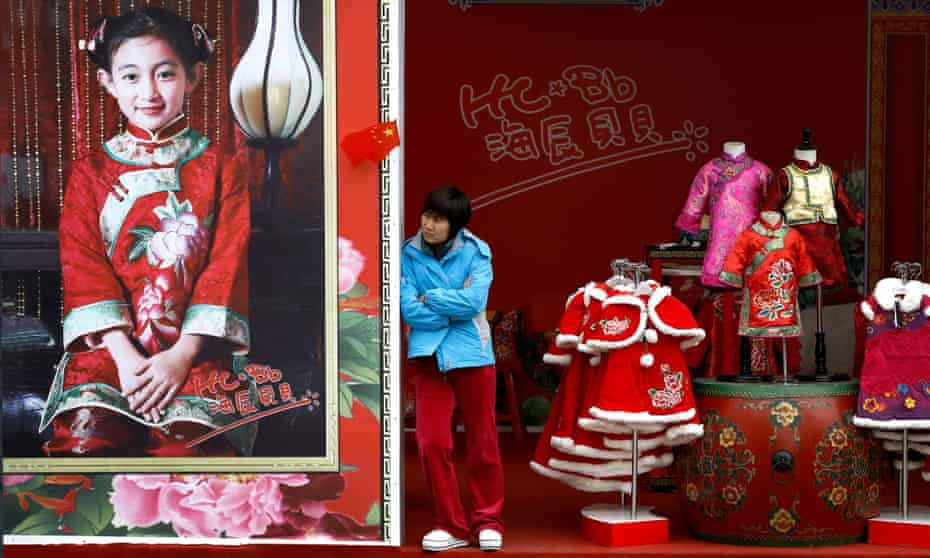 A woman waits for customers at a children's clothing store in the Wangfujing shopping district of Beijing.
