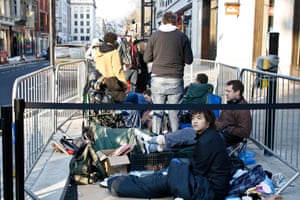 People wait in line outside the Apple store