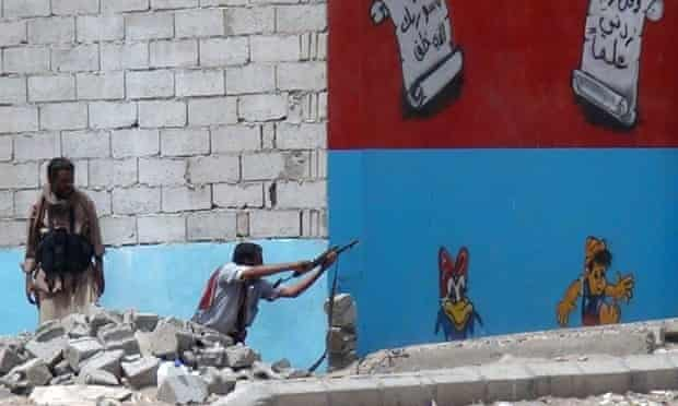 A Yemeni fighter opposing the Houthi rebels fires his weapon in Aden as clashes continue.