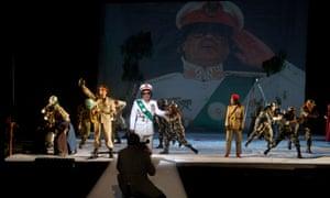 "Ramon Tikaram (centre) as Gaddafi, and Sharon Duncan-Brewster (right) as Fatima, at the English National Opera in ""Gaddafi: A Living Myth"""