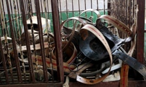 The metal jackets taken off from bears are put in a cage at a bear bile farm in Weihai city, east Chinas Shandong province, 19 April 2010. The illegal metal jacket had just been taken off by the farmer in Weihai in eastern Chinese province of Shandong, and flung into a corner.