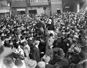 1937 Royal Mail, ridden by Evan Williams, is led in through a big crowd after winning the Grand National