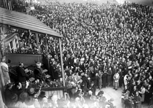1921 The crowd at Aintree cheer the arrival of King George V and Queen Mary in the Royal Box