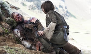 An injured Sandor Clegane, better known as The Hound and Arya Stark in a scene from season four of Game of Thrones.