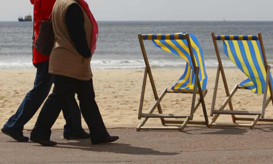 Pensioners walk along a beach promenade.