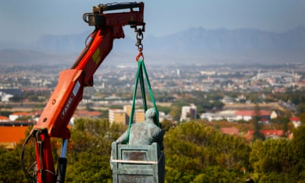 The statue being lifted away by a crane