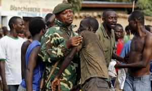 A military officer tangles with protesters in Burundi's capital, Bujumbura.