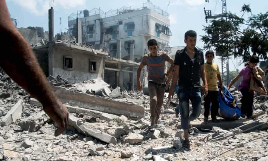 A group of Palestinian children and teenagers rescue possessions from a devastated area of northern Gaza during a ceasefire in last summer's summer's war.