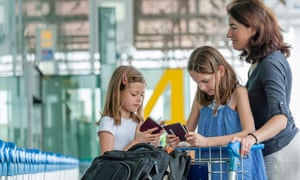 Mother and daughters standing at airport.