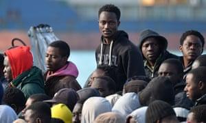 Rescued migrants disembark the Italian Guardia di Finanza vessel at the Sicilian harbour of Catania on April 23, 2015.