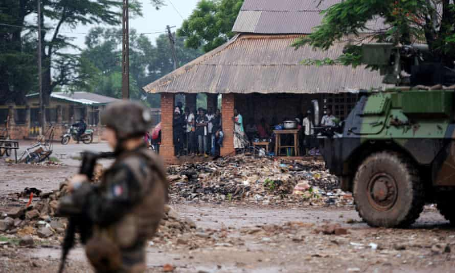 French soldiers of the Sangaris force patrol as locals take shelter from the rain on July 8, 2014 in the Fatima area of Bangui.