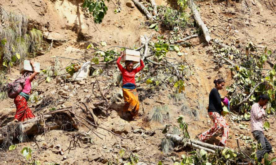 People cross a landslide zone after collecting relief material in Baluwa village, Gorkha district, close to the epicentre of the 25 April earthquake. Villagers were distributing emergency provisions among themselves on 30 April, as official aid and rescue operations continued to be held up.