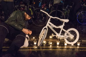"A man lights candles beside a ""ghost bike"" memorial in London."