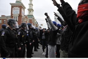 Protesters stand with raised hands facing police during protests over the death in custody of Freddie Gray on April 27