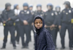 A boy stands in front of a police cordon April 27