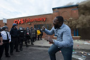 A man shouts in front of a police line beside a CVS pharmacy that caught on fire after being looted on April 27