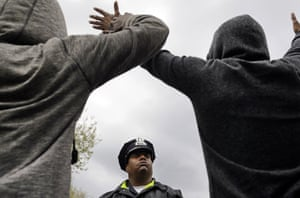 A member of the Baltimore Police Department stands guard outside of the department's Western District police station as men hold their hands up in protest on April 22
