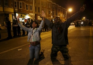 People gesture while kneeling along Pennsylvania Avenue, past the curfew, on April 29
