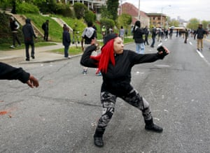 A woman throws rocks at Baltimore police on April 27 Stapleton:rel:d:bm:GF10000075216