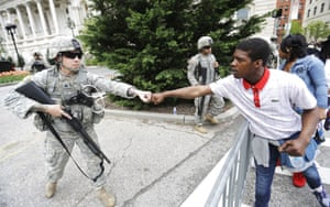 Brandon Payton, right, of Baltimore, fist-bumps a National Guardsman standing outside of City Hall as protesters march on April 30