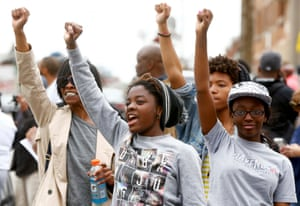 People celebrate as they gather in the streets of Baltimore following the decision to charge six police officers, including one with murder, over the death of Freddie Gray on May1