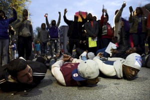 Demonstrators pretend to be arrested in front of the Baltimore Police Department Western District station on April 23