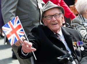 A war veteran waves a flag in the parade