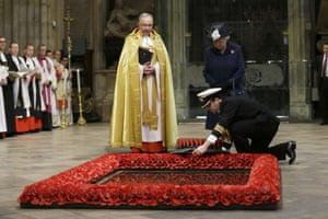 Queen Elizabeth II watches as a wreath is laid on her behalf at the tomb of the Unknown Warrior flanked by the Dean of Westminster, John Hall, at the start of a service at Westminster Abbey