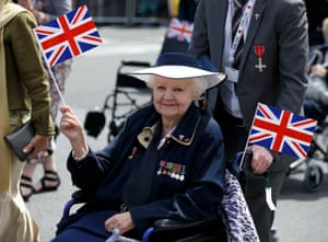 A veteran holds a flag during an armed forces and veterans' parade on the final day of the commemorations of the 70th anniversary of Victory in Europe (VE) Day