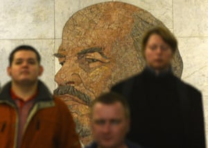 Subway passengers walk past a huge portrait of the Soviet Union founder Vladimir Lenin in a vestibule of the Biblioteka Imeni Lenina metro station in Moscow.