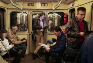 People using their tablets on a Moscow metro train.
