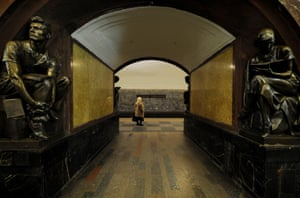 A woman waits on a platform at Ploshchad Revolutsii metro station.