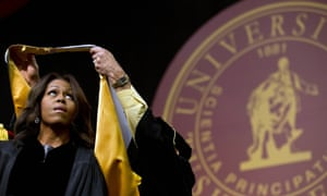 Michelle Obama is presented with a robe and honorary degree at the Tuskegee University's spring commencement.