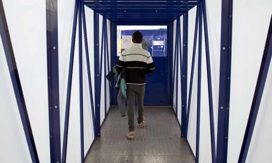 An asylum seeker walks between emergency accommodation shelters for applicants awaiting refugee status in Berlin.