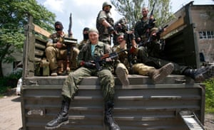 Pro-Russian separatist fighters sit in a truck as they set out from a base in the eastern Ukrainian city of Donetsk.