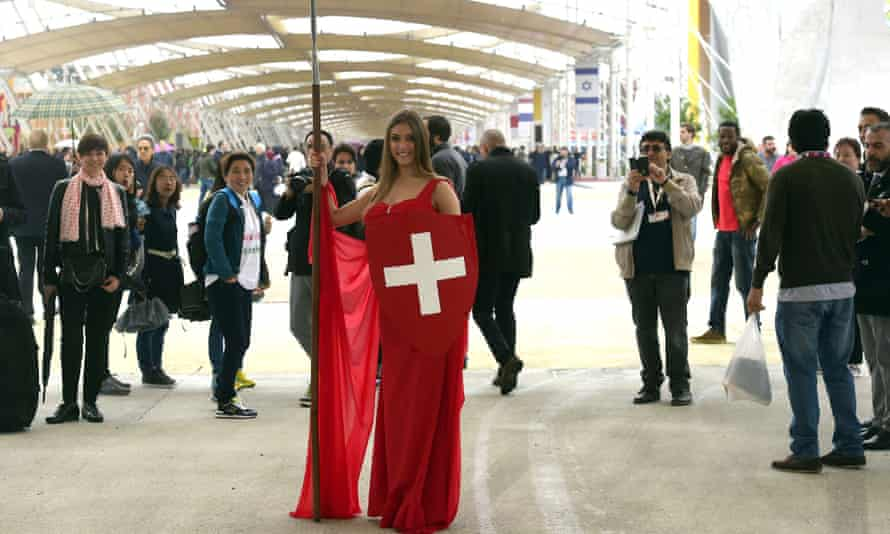 A model poses next to the Swiss pavilion on the opening day of Expo 2015.