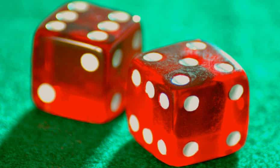 A pair of casino red dice on a green casino table.  Luckwarmers effectively want to bet our future on the dice coming up showing snake eyes.