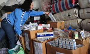 A Romanian customs officer shows seized smuggled cigarettes.