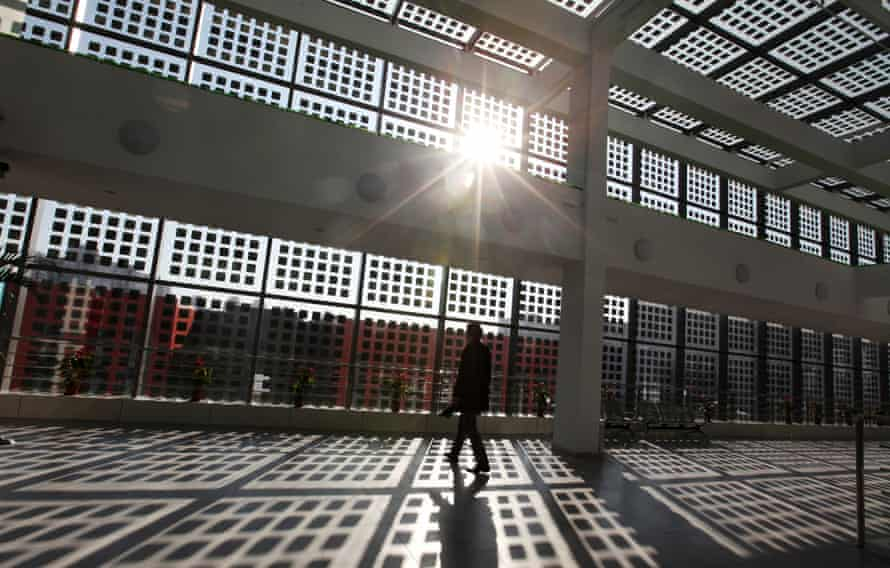A man walks in a building with solar panel glass windows in the Sino-Singapore Tianjin Eco-city in Tianjin Binhai New Area, China, 30 November 2011.