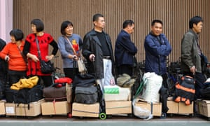 Shoppers from mainland China wait in a queue with their purchases in Hong Kong.