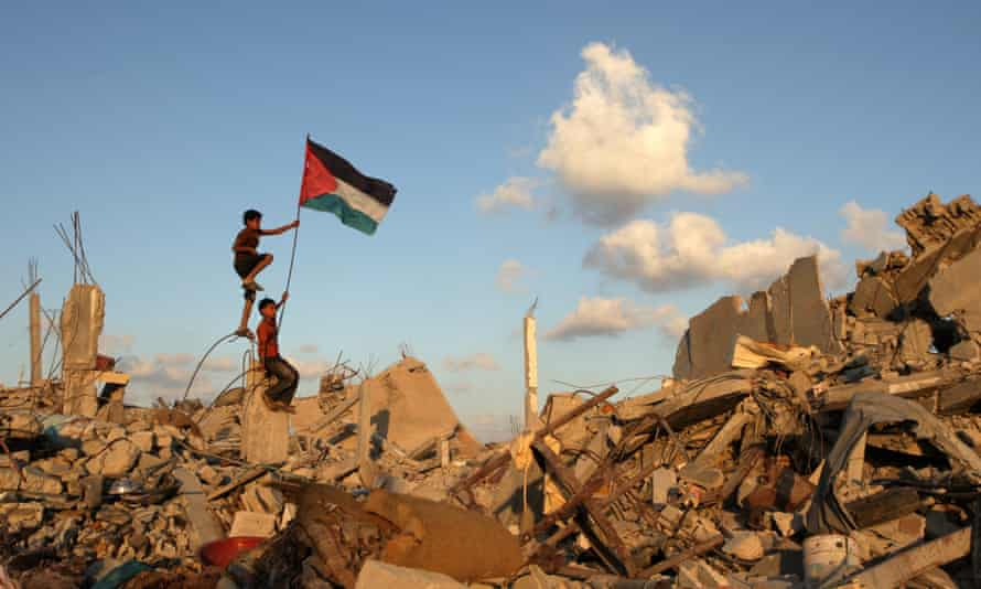Palestinian children place their national flag on the rubble of a building which was destroyed during the Israeli army summer's military offensive on in Khan Yunis, Gaza Strip.