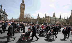 Veterans walking and in wheelchairs passing by Big Ben in a parade