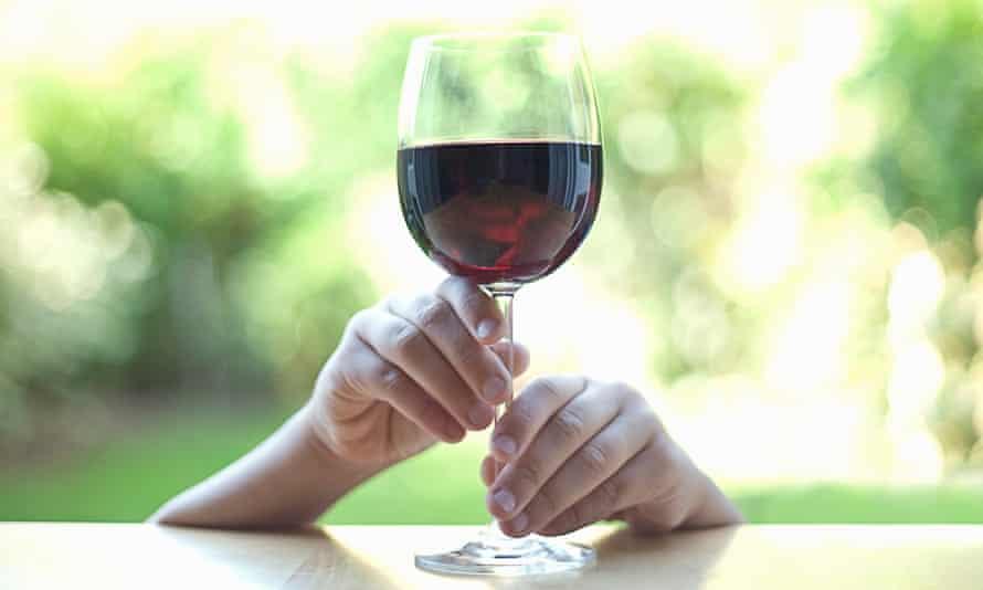 Hands holding stem of wine glass