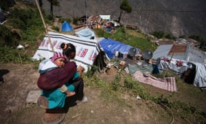 A woman and child sit near a temporary shelter in Dhunche, Nepal.