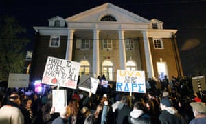 Protestors carry signs and chant slogans in front of the Phi Kappa Psi fraternity house at the University of Virginia, Saturday night, November 22, 2014, in Charlottesville, Virginia. UVA dean Nicole Eramo filed suit on Tuesday, claiming that the article that initiated the protests was malicious and defamatory.