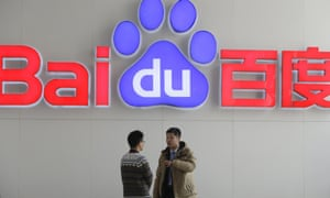 People talk in front of Baidu's company logo at its headquarters in Beijing, China.