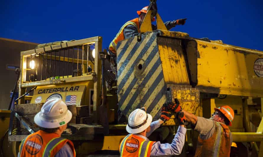 Workers prepare heavy machinery to remove the train.