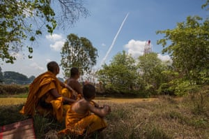 Monks observe a rocket launch from a distance