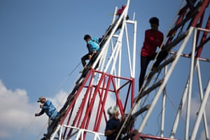 Teams climb up scaffolding structures to mount their rockets